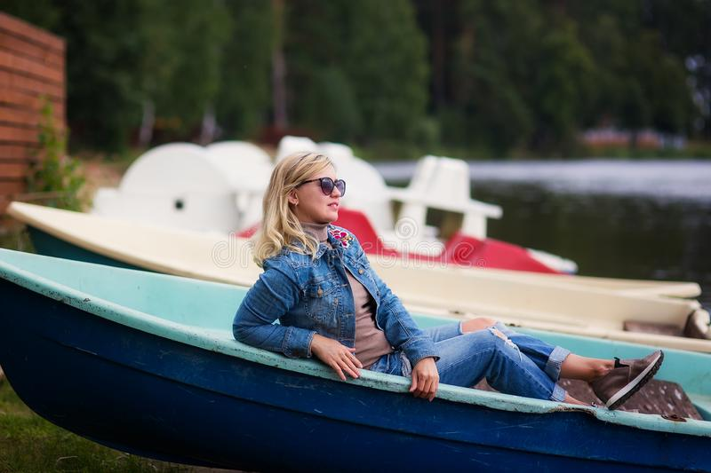 Pretty woman poses on fishing boat in a calm lake water. Old fishing boat. Fishing boat at Lake royalty free stock images