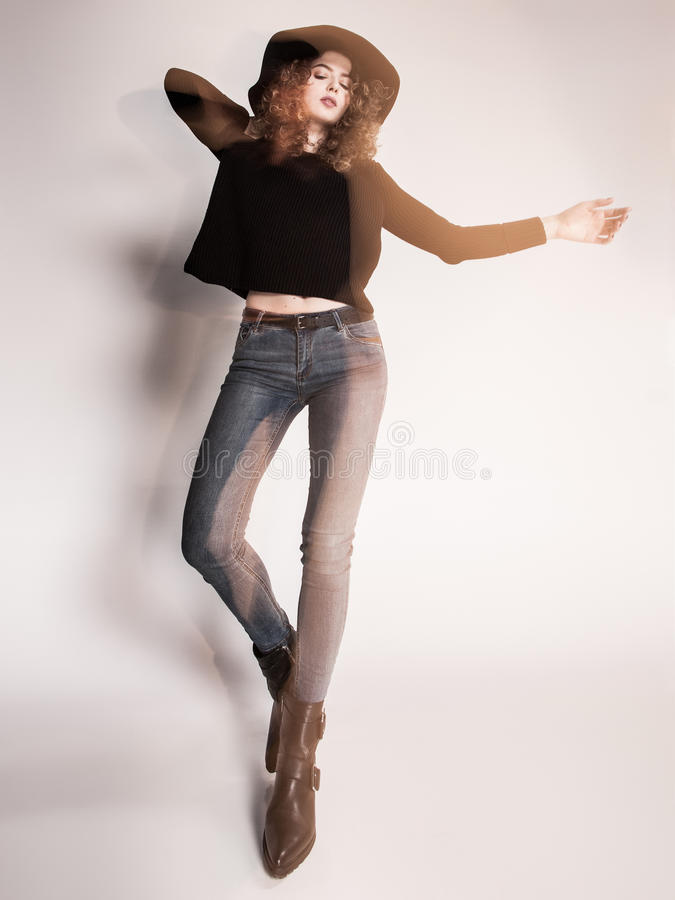 Pretty woman posing in denim pants and boots and black hat - intentional motion blur. Pretty woman posing in denim pants and boots and black hat -intentional stock image