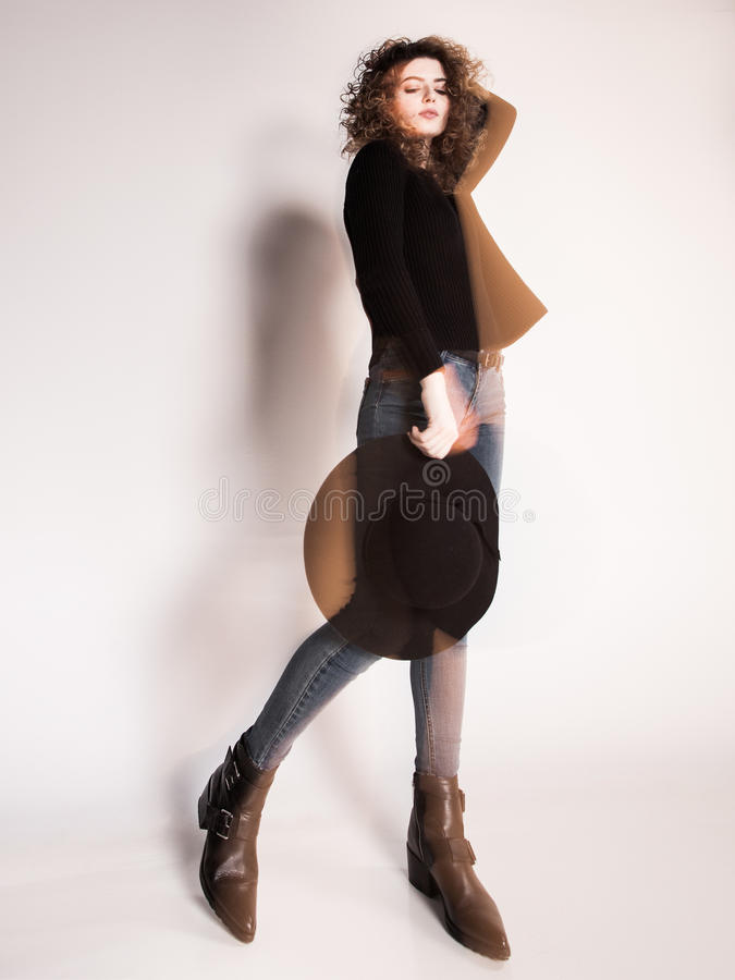 Pretty woman posing in denim pants and boots and black hat - intentional motion blur. Pretty woman posing in denim pants and boots and black hat -intentional royalty free stock image