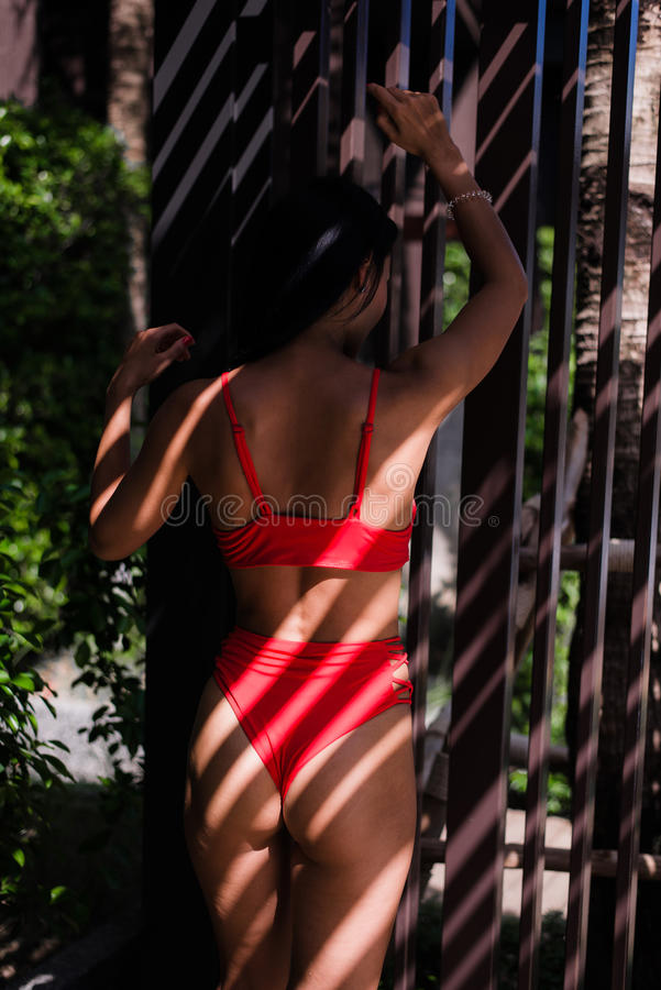 Pretty woman posing in swim suit, outdoor fashion portrait with artistic shadow light at summer near swimming pool stock images
