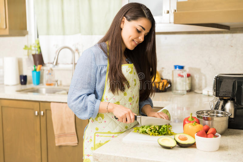 Pretty woman preparing some food at home. Beautiful young woman chopping vegetables and cooking some food at home stock photos
