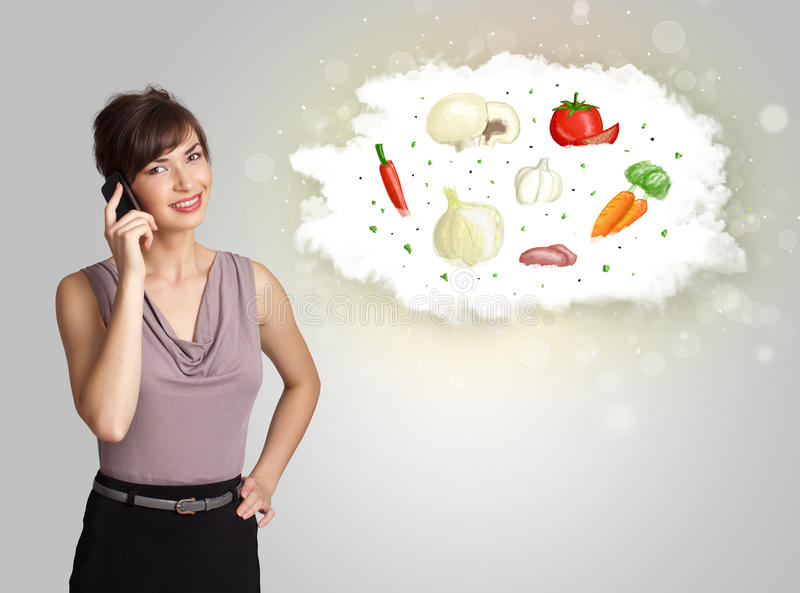 Pretty woman presenting a cloud of healthy nutritional vegetable royalty free stock images