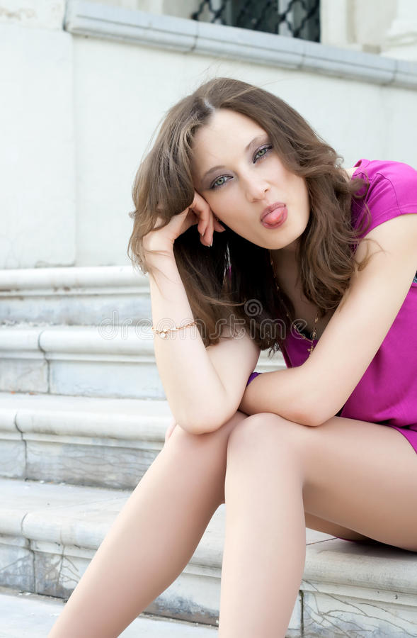 Pretty woman puts out tongue. royalty free stock images