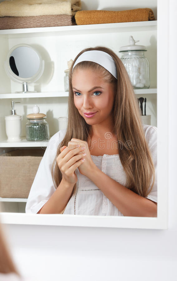 Pretty woman putting cream on her hands stock photos