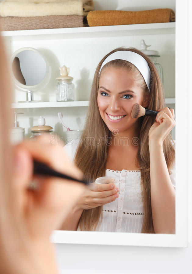 Pretty woman putting makeup on royalty free stock photography