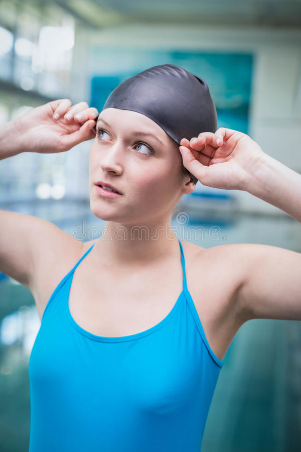 Pretty woman putting on swim cap. At the pool stock image