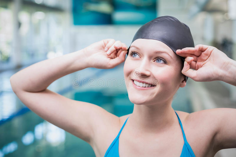 Pretty woman putting on swim cap. At the pool royalty free stock photo