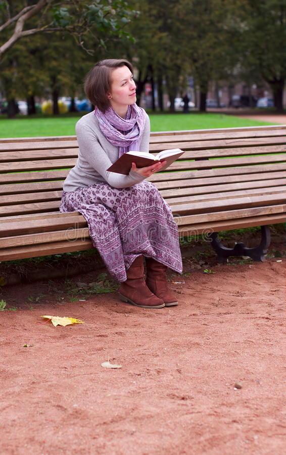 Download Pretty Woman Reading A Book On Bench And Thinking Stock Photo - Image: 21649992