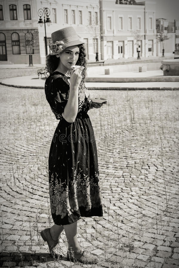 Pretty woman in retro dress and hat drinking hot drink or bever stock photography