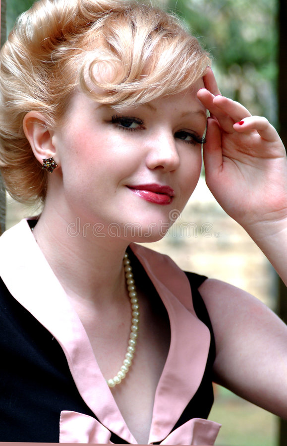 Pretty Woman Saluting. Closeup of young blond woman with hand on forehead, saluting stock photography