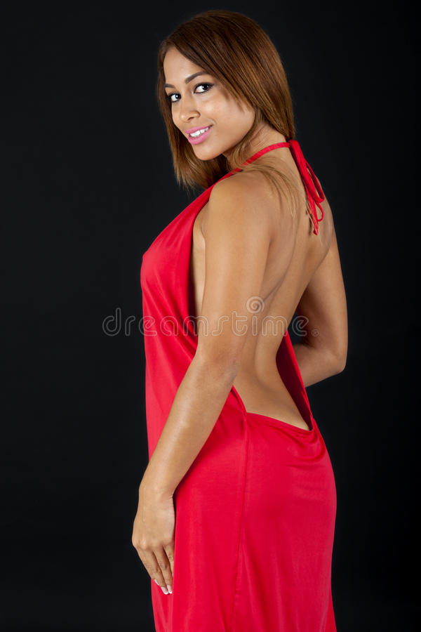 Pretty woman in a red dress. Pretty woman in a low cut back red dress. Shot on black background royalty free stock photo