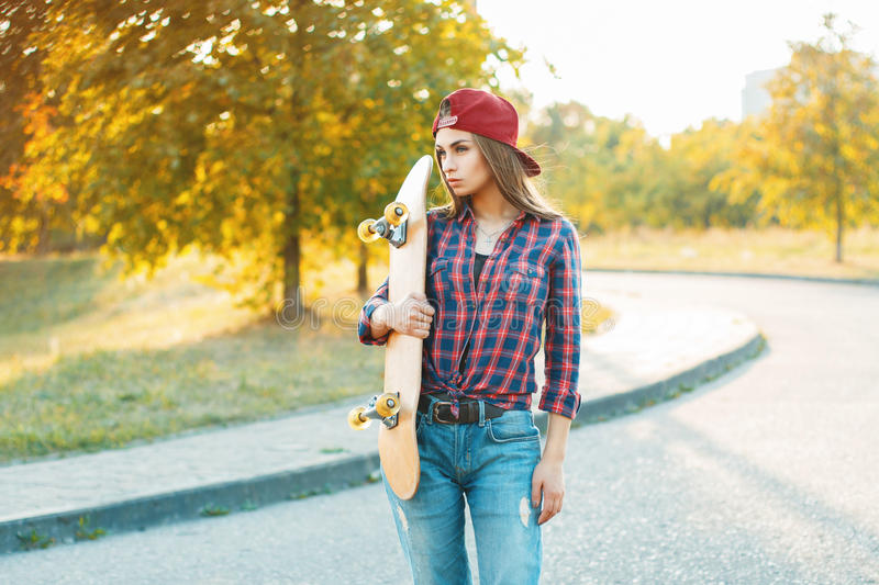 Pretty woman in shirt and jeans holding a skateboard. Beautiful stock image