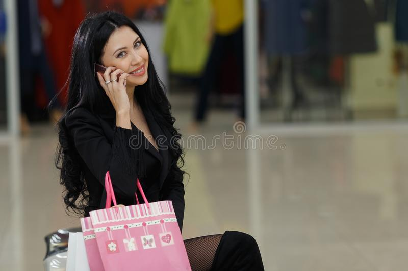 Pretty woman with shopping bags talking on mobile phone in the mall. royalty free stock photography