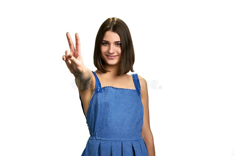 Pretty woman showing peace with fingers. stock photos
