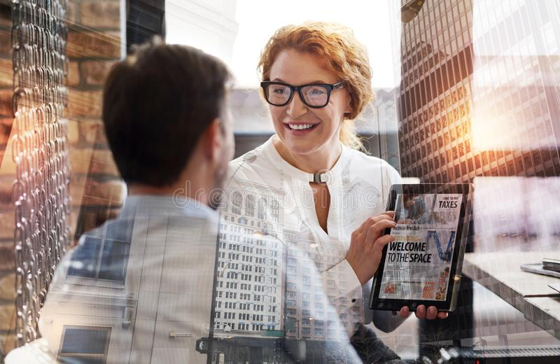 Pretty woman showing tablet with news article to her boss stock photo