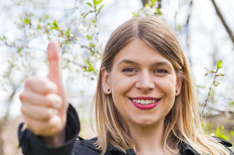 Pretty woman showing thumbs up in the blooming garden royalty free stock images