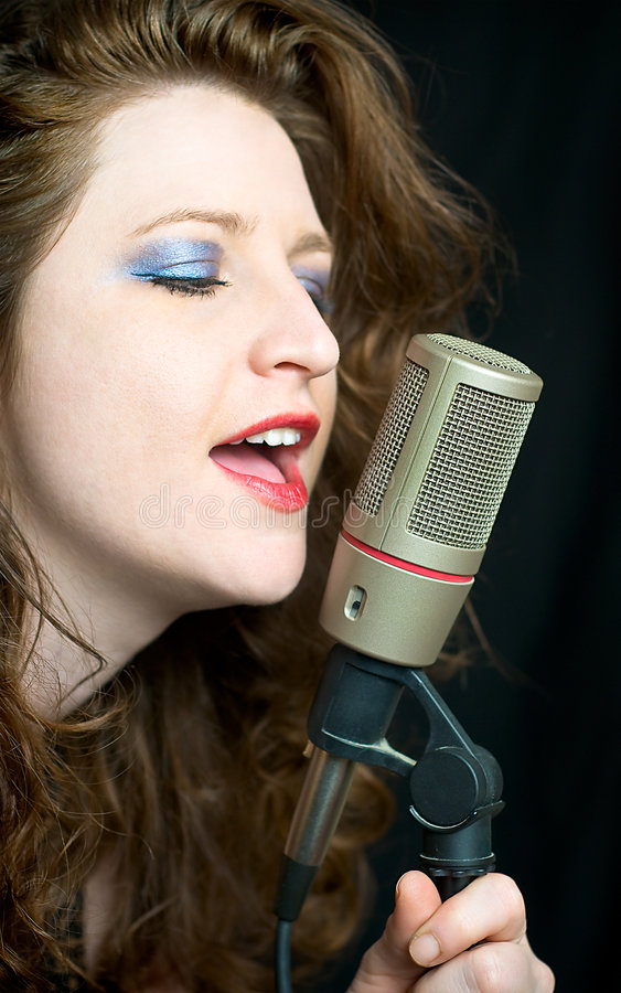 Pretty Woman Singing Into Microphone. With Red Lipstick royalty free stock photography