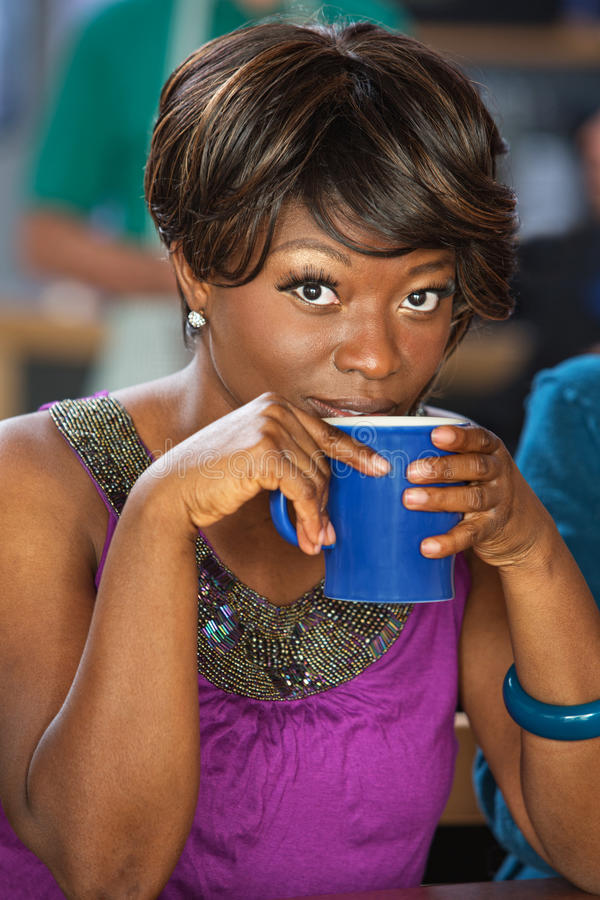 Pretty Woman Sipping Coffee. Pretty African woman sipping from coffee mug stock photo