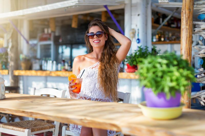 Pretty woman sits at the bar and enjoys a drink stock photo