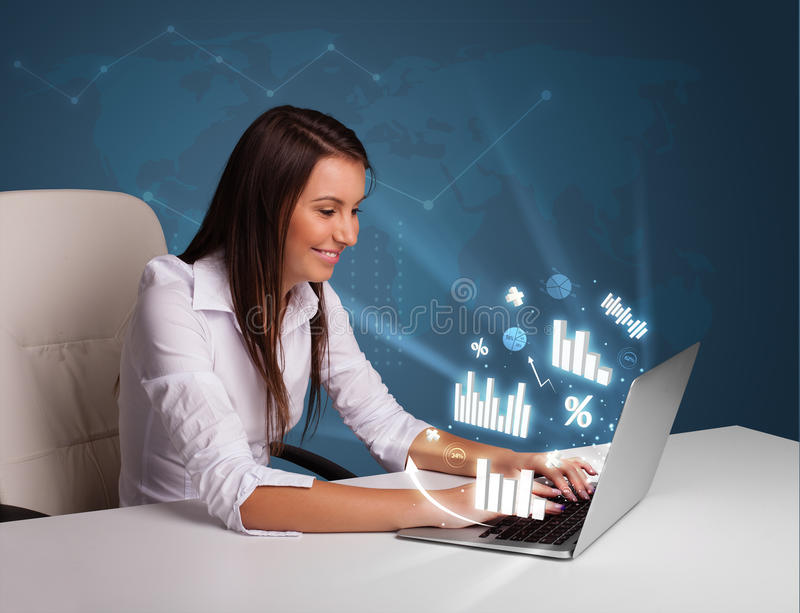 Pretty woman sitting at desk and typing on laptop with diagrams. And graphs comming out stock images