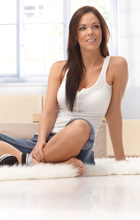Pretty woman sitting on floor at home smiling stock images