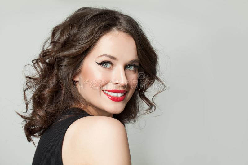 Pretty woman smiling. Happy brunette model girl with makeup and brown curly haircut portrait stock photo