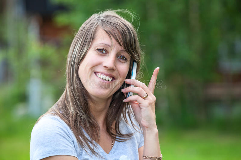 Pretty woman smiling then calling on phone. Young pretty Caucasian female smiling then calling on the mobile phone. Copyspace royalty free stock images