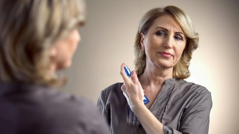 Pretty woman spraying perfume in front of mirror, preparing for date in her 50s royalty free stock photos