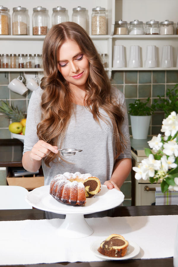 Pretty woman sprinkle castor sugar on the cake. Beautiful smiling woman sprinkling icing sugar on the top of the cake royalty free stock photo