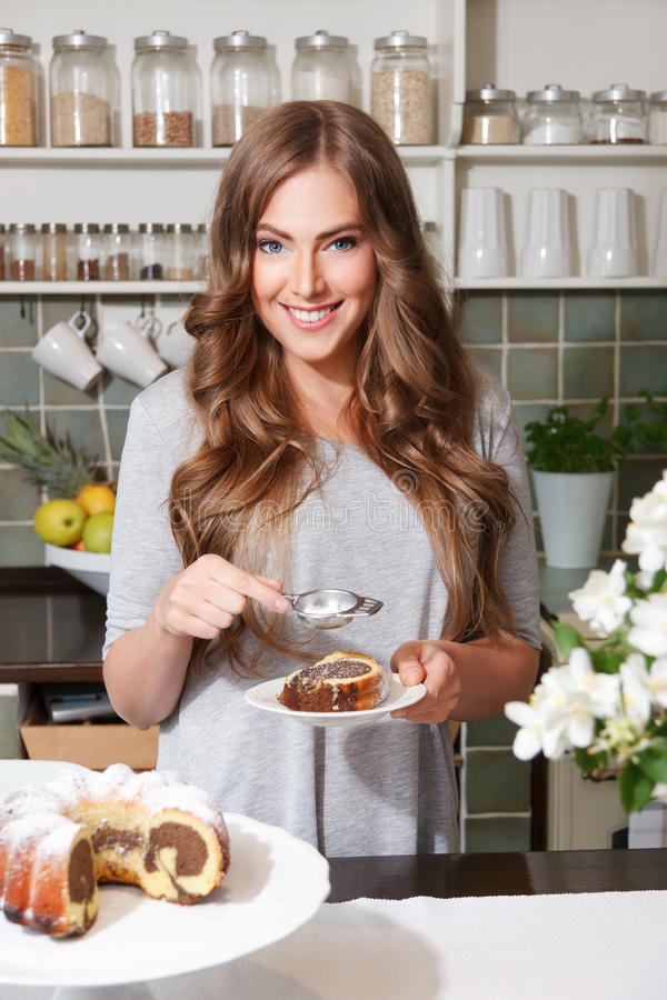 Pretty woman sprinkle icing sugar on the cake. Pretty woman sprinkle icing sugar on the top of the cake stock image