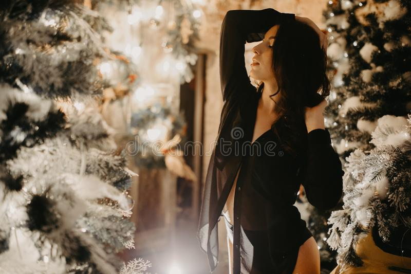 Pretty woman stands against background of Christmas decorations. Pretty young woman in transparent black shirt stands against the background of Christmas stock images