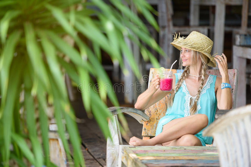 Pretty woman with straw hat sitting in the tropical shade royalty free stock photos
