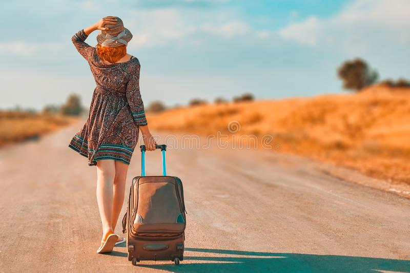 Beautiful woman hitchhiking. Pretty woman in summer dress and hat hitchhiking with suitcase. Girl walking on the road with Luggage at fall. Journey royalty free stock photography
