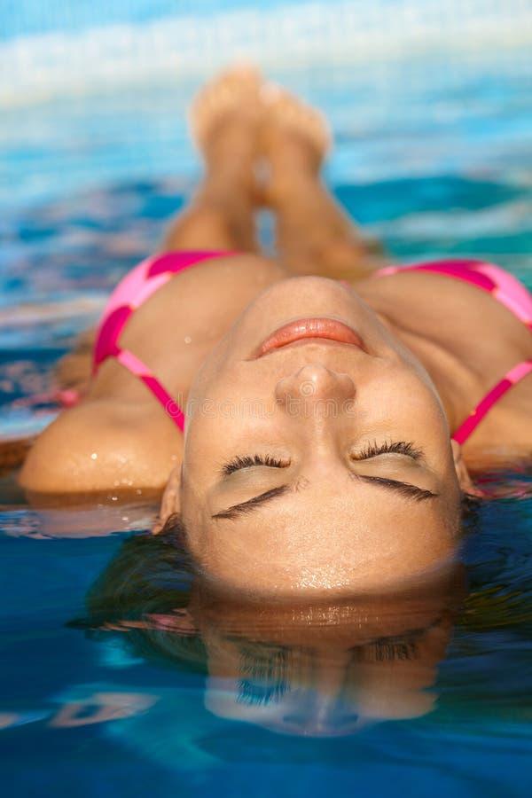 Pretty woman sunbathing in water stock images