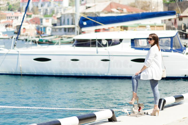 Pretty woman in sunglasses on the pier near luxury yachts. Happy girl in sunglasses. Summer sunny day. royalty free stock photo