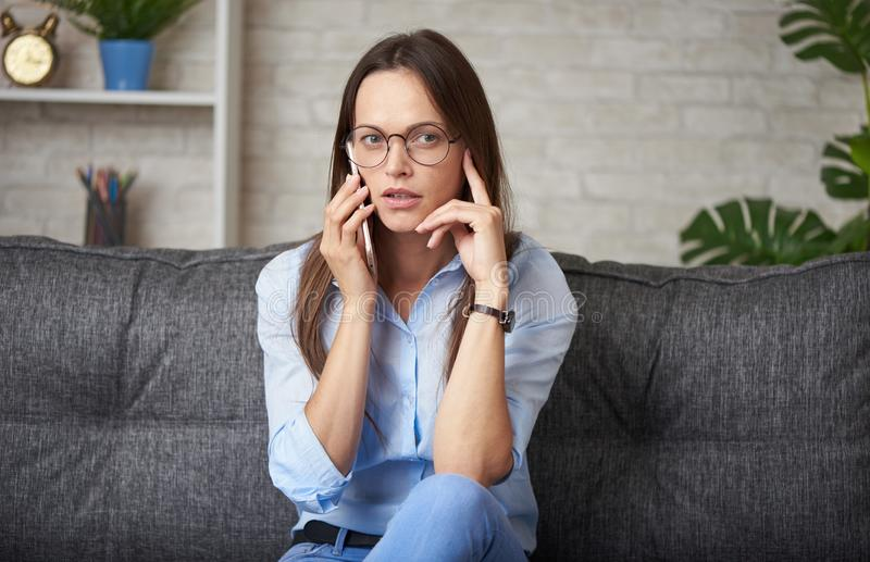 woman is talking on smartphone at home stock photo