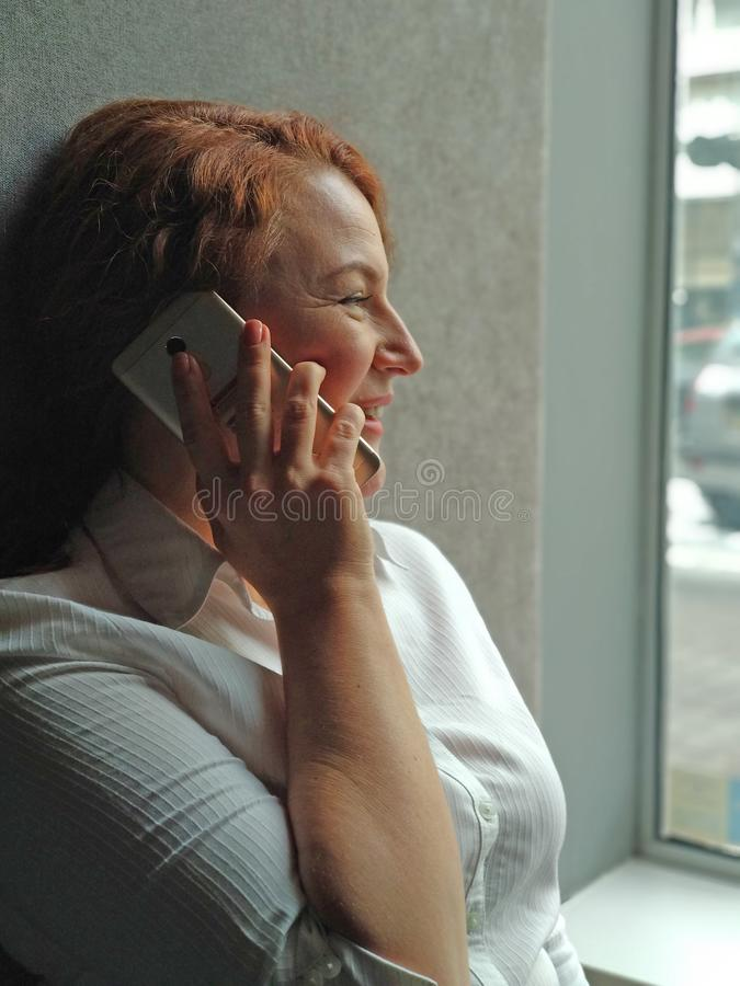 Pretty woman talks on phone in front of panoramic windows in business center. Happy woman talks about happy life stock images