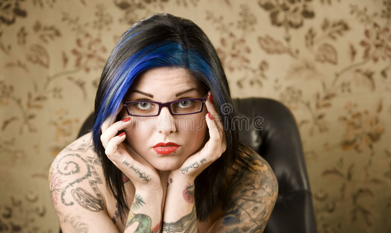 Pretty Woman with Tattoos in a Leather Chair. Pretty young woman with many tattoos in a leather chair stock image
