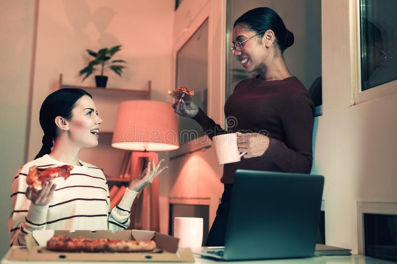 Pretty woman telling her friend interesting story. Just imagine. Pretty young women telling her friend interesting story having dinner at the office stock photo