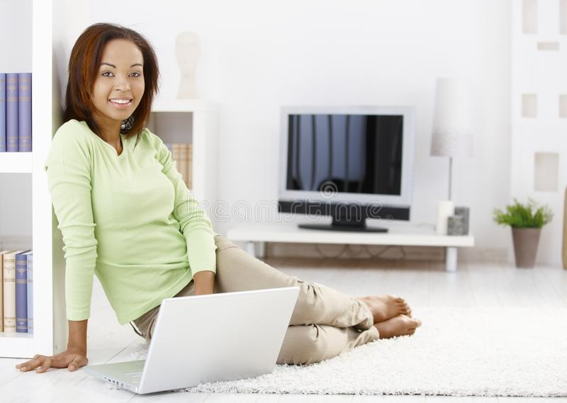 Pretty woman using computer at home. Pretty woman using laptop computer at home, sitting on living room floor, smiling at camera royalty free stock photo