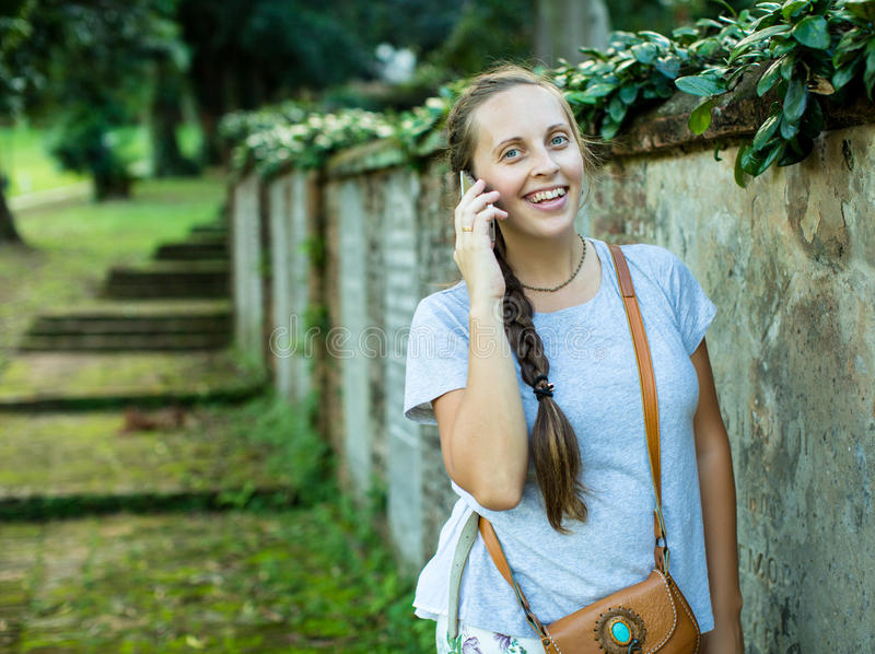 Pretty Woman using her Phone in the Park stock image
