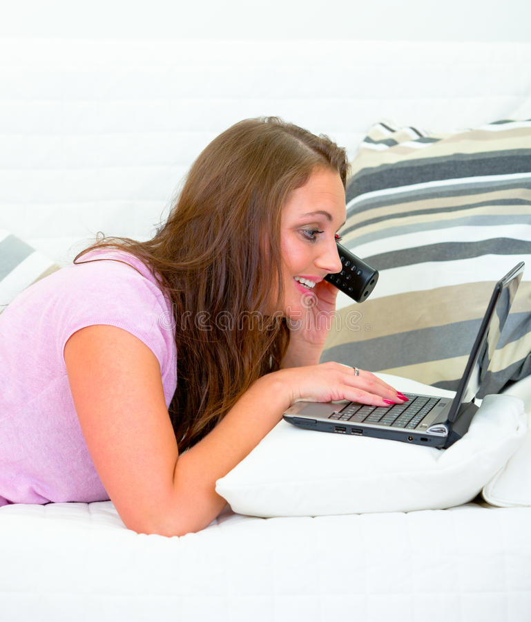 Pretty woman using laptop and talking on phone stock image
