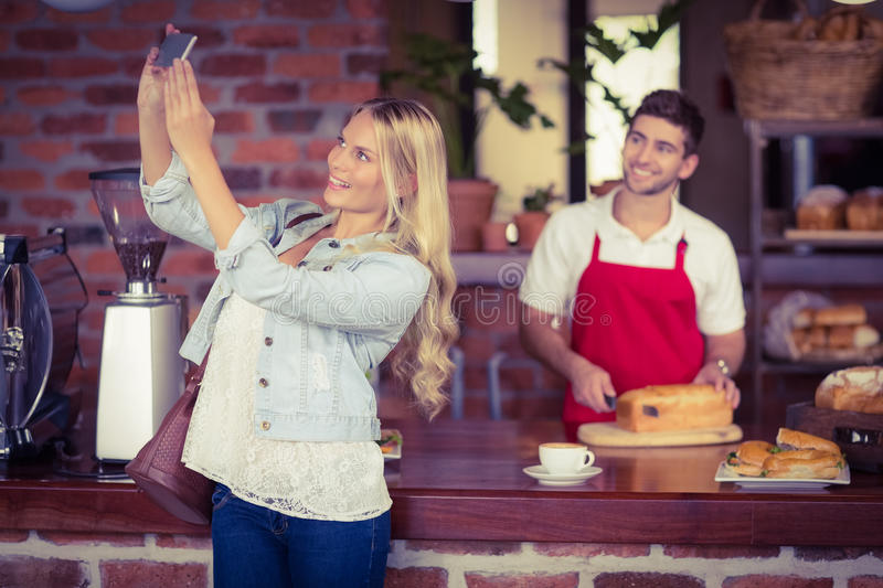 Pretty woman and waiter taking a selfie stock photos