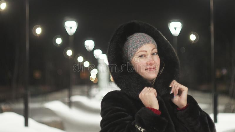 Pretty woman walking along the black fur coat. Outdoor. Girl walks on a winter night among the street lights of the city royalty free stock image