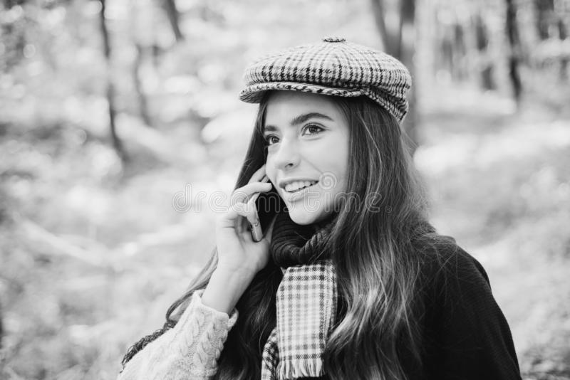 Pretty woman walking in the Park and talking on mobile phone. Autumn woman having fun at the park and smiling. 4g, 5g stock image