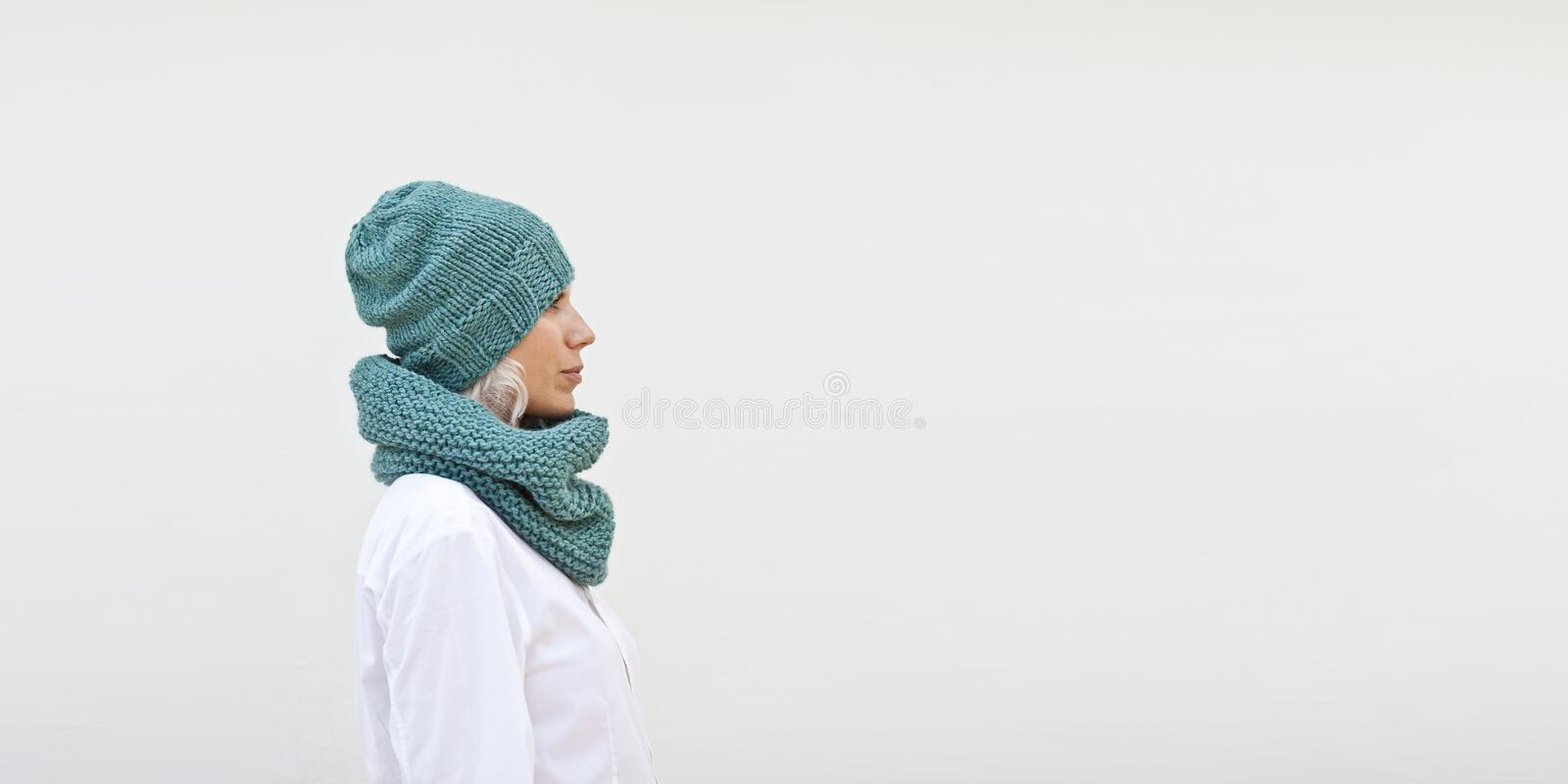 Pretty woman in warm turquoise knitted hat. And snood royalty free stock photo
