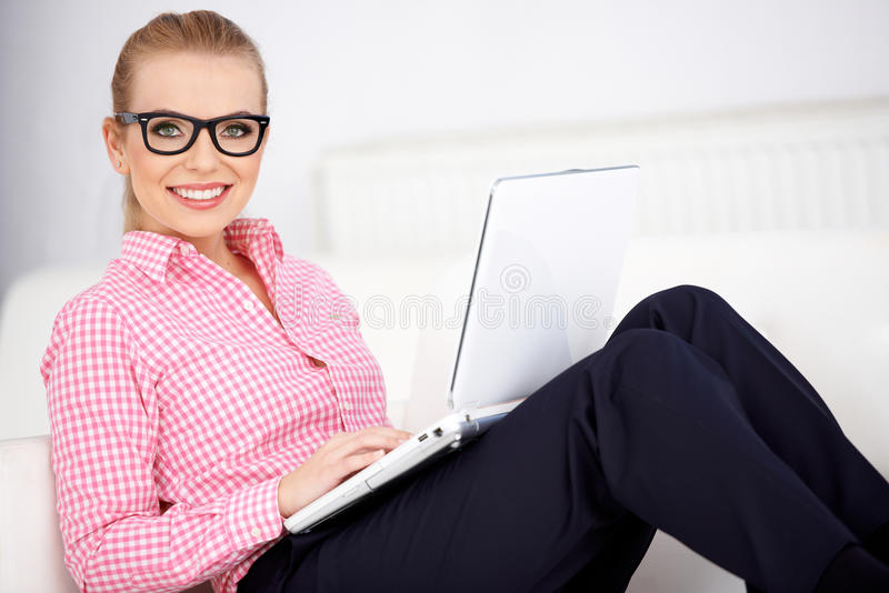 Pretty woman wearing glasses relaxing at home stock photography