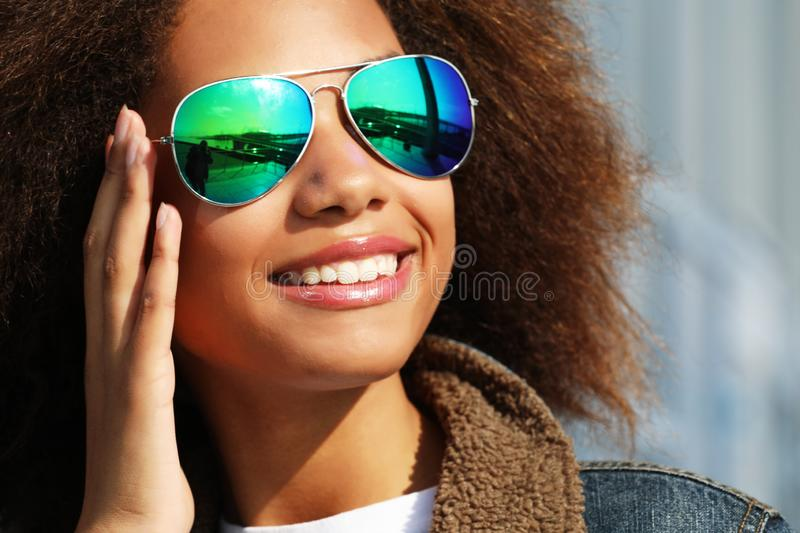 Pretty woman wearing sunglasses with perfect teeth and dark clean skin having rest outdoors stock photography