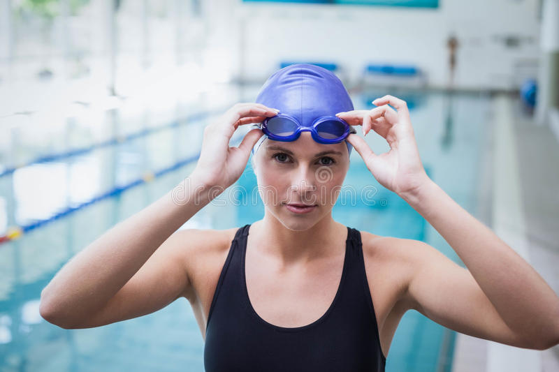 Pretty woman wearing swim cap and goggles. At the pool stock photos