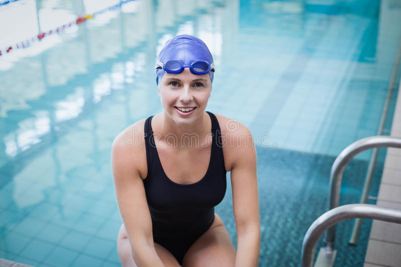 Pretty woman wearing swim cap and goggles. At the pool royalty free stock images